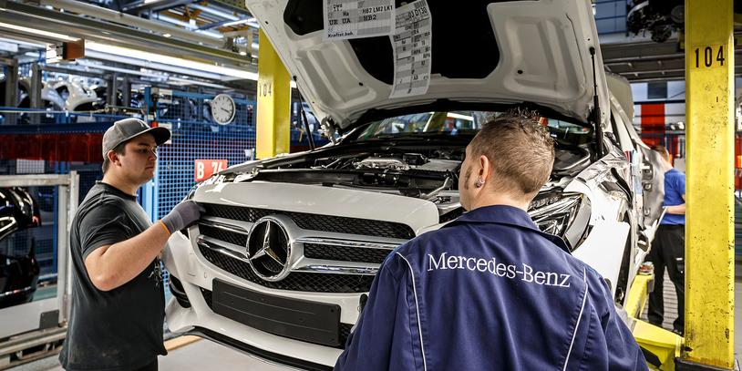 Zwei junge Männer bei der Montage eines weißen Mercedes: Produktion der C-Klasse im Mercedes-Benz Werk Bremen.