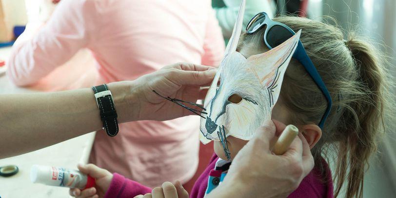 Ein Kind mit einer selbst bemalten Fuchs-Maske.