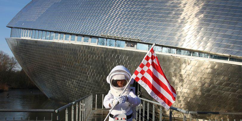 Frau im Astronautenkostüm vor dem Universum® Bremen