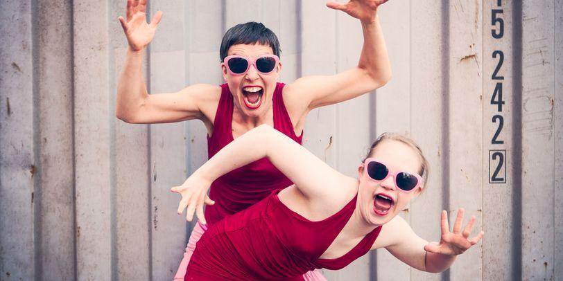Zwei Tänzerinnen in roten Kleidern und mit rosa Sonnenbrillen bei einer Tanzperformance.