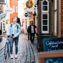 Ein Rad neben sich her schiebend, schlendert eine junge Frau durch eine Gasse im Schnoor.
