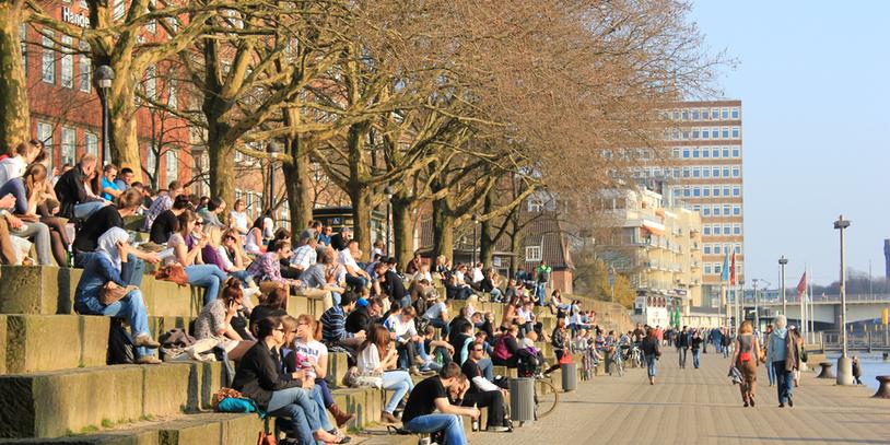 Menschen sitzen auf den Stufen vor der Schlachte in der Sonne