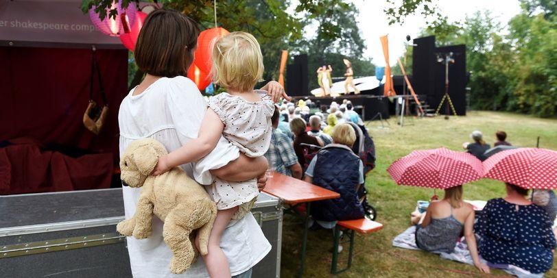 Eine Mutter hält ihre Tochter auf dem Arm und sie sehen sich gemeinsam ein Stück auf der Bühne an.