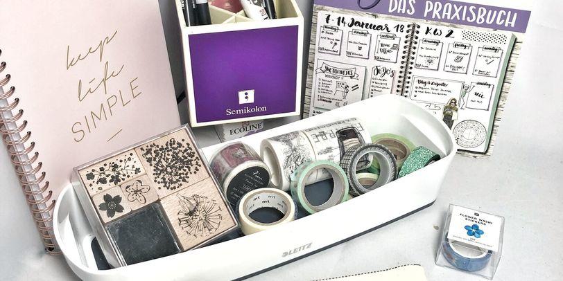 """Auf weißem Untergrund stehen zwei Notizbücher in rosa und lila, eine weiße Schale mit buntem Klebeband, eine lila Box mit Stiften sowie ein Stoffmäppchen mit der Aufschrift """"SKETCH NOTES by Diana"""""""