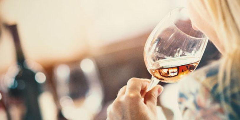 Eine Frau riecht an einem Glas Wein
