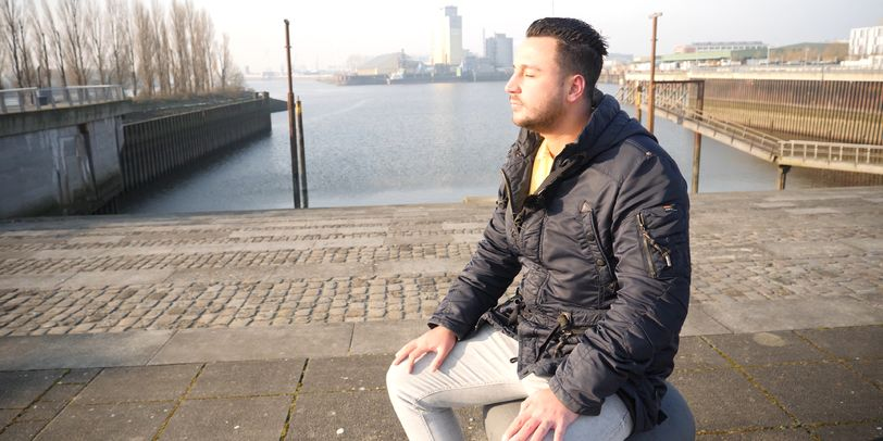 Eine männliche Person sitzt auf einem Poller. Im Hintergrund sind Steinstufen zu sehen, die zum Wasser führen. Am Horizont sind Industriegebäude zu erkennen.