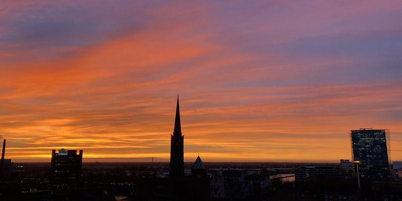 Ein in orange gefärbter Himmel, vor dem sich Gebäude und ein Kirchenturm abzeichnen.