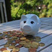 Ein Sparschwein und jede Menge Kleingeld liegen auf einem Tisch