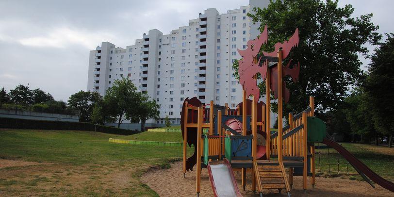 Blick auf einen Kinderspielplatz, im Hintergrund eine große Wohnanlage
