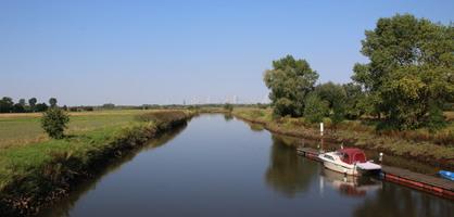Blick auf die Ochtum in Bremen Strom, an einem Steg liegt ein Boot, blauer Himmel
