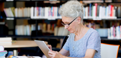 Eine ältere Dame sitzt mit ihrem iPad in der Bibliothek und studiert