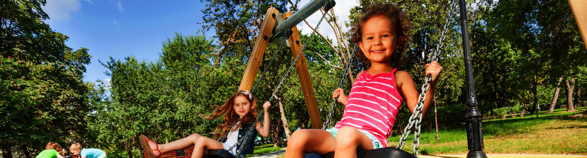 Zwei Mädchen schaukeln auf einem Spielplatz