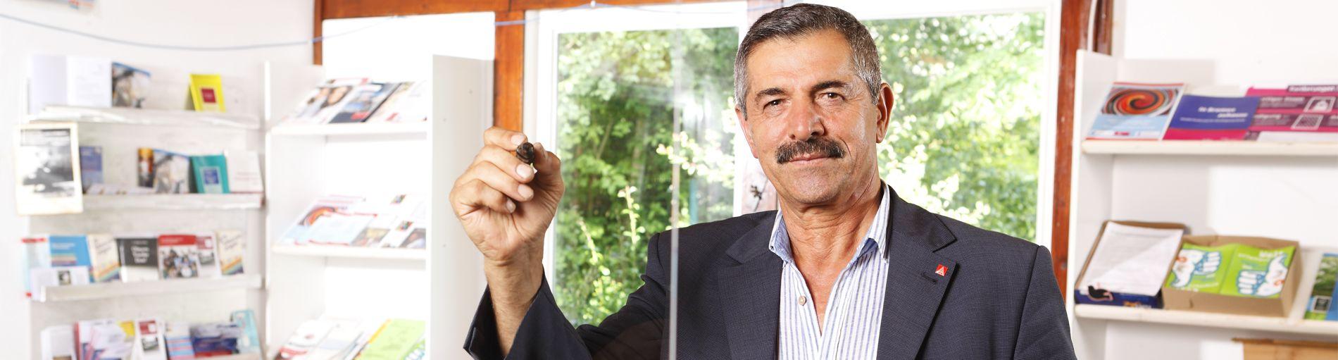 Portraitbild eines Mannes mit Stift in der Hand