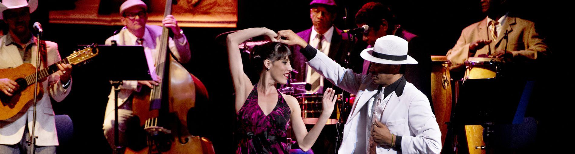 Auf dem Bild sind ein tanzendes Paar abgebildet. Die Frau trägt ein lilanes Kleid und der Herr einen weißen Anzug mit Hut. Die beiden befinden sich gerade mitten in einer Drehung und hinter ihnen sieht man die Band spielen.