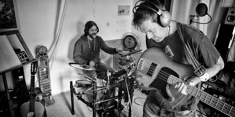 Zwei Männer sind mit vielen Instrumenten in einem Aufnahmestudio.