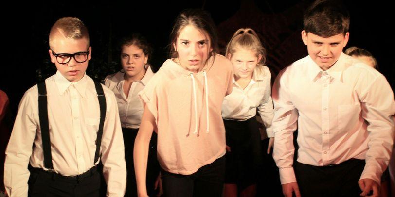 """Eine Szene aus dem Theater elf Stück """"Reine Herzen"""". Fünf junge Schauspieler laufen ernst auf die Kamera zu"""