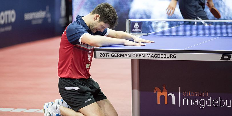 Der Athlet Dimitrij Ovtcharov betet an einer Tischtennisplatte.