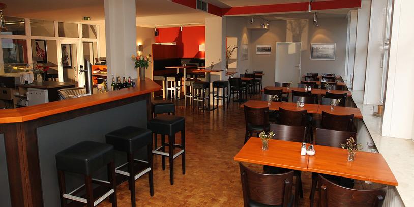 Eine Innenansicht des Lokals ÜberBlick mit hölzernen Tischen und Stühlen; Quelle: ÜberBlick