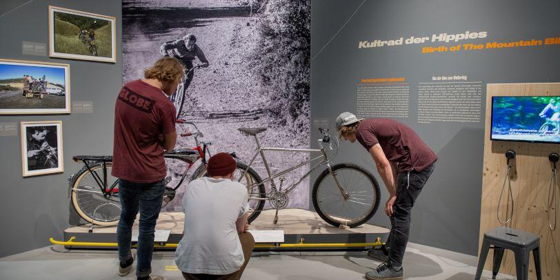 Drei junge Männer schauen sich in der Sonderausstellung des Universum Bremen Fahrräder an.