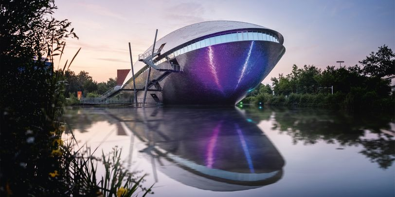 Ein futuristisches Gebäude mit einem See