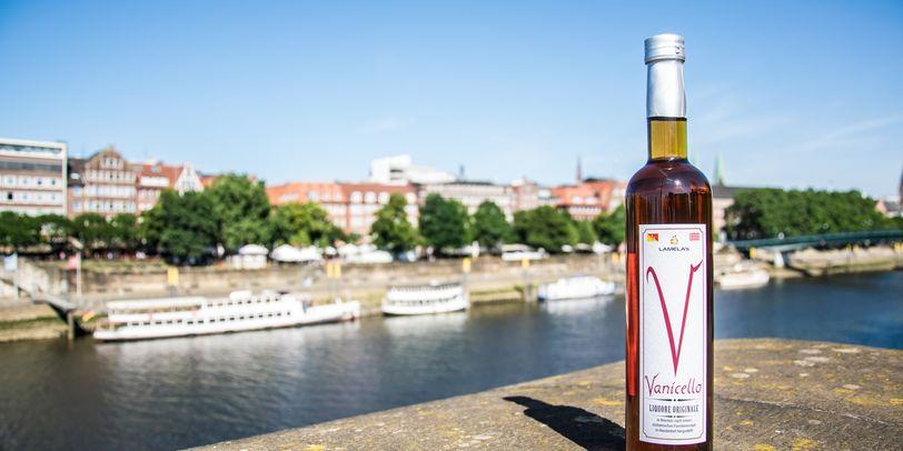 Eine Flasche Vanicello auf einer Mauer, im Hintergrund Weser und Schlachte