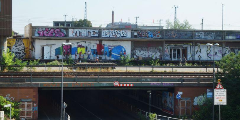 Graffitis sind von der Straße über einer Unterführung zu sehen.