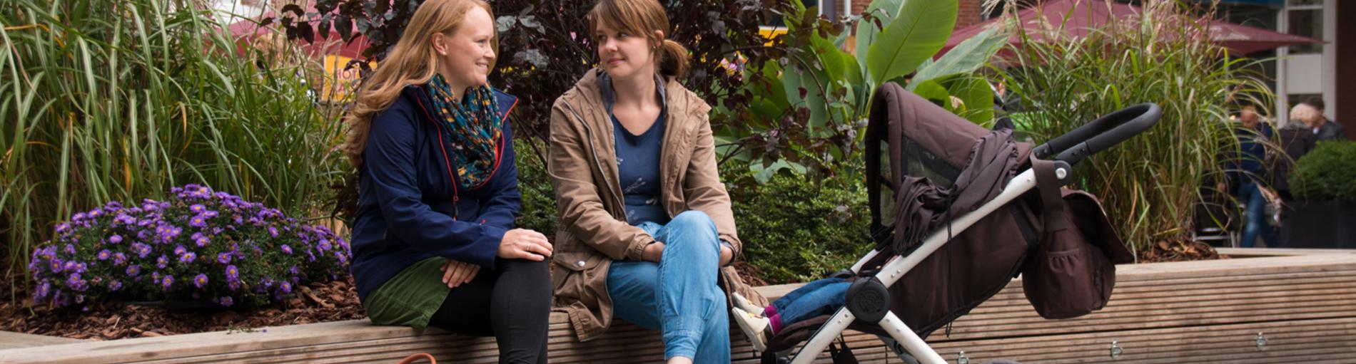Zwei Frauen sitzen am Ansgarikirchhof und unterhalten sich, neben sich ein Kinderwagen.