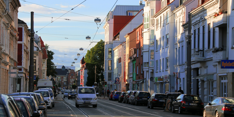 Blick auf eine Straße in der Abendsonne, Autos parken am Straßenrand