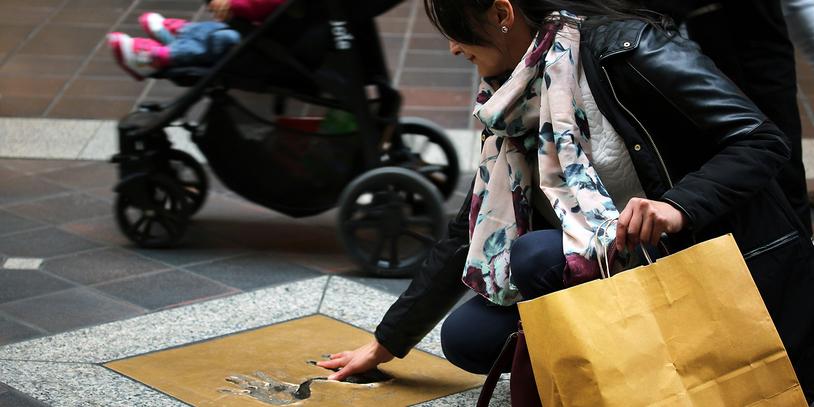 Eine Frau hält Ihre Hand in einen Handabdruck auf der Mall of Fame