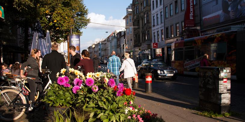 Menschen treffen sich im Viertel, im Vordergrund bunte Blumen eines Blumenstandes