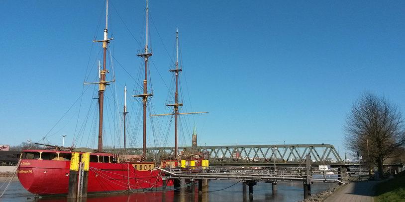 Ein roter Windjammer liegt an einem Anleger an der Weser