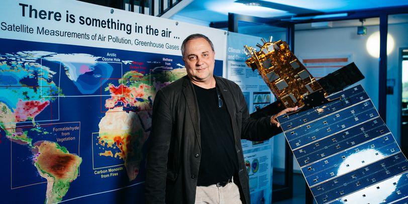 Ein Mann hält einen Satelliten. Hinter ihm ist eine Darstellung der Kontinente.