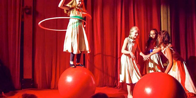 Vier Mädchen auf der Bühne, eines steht auf einem großen Ball und schwingt einen Hula-Hoop-Reifen um die Hüfte.
