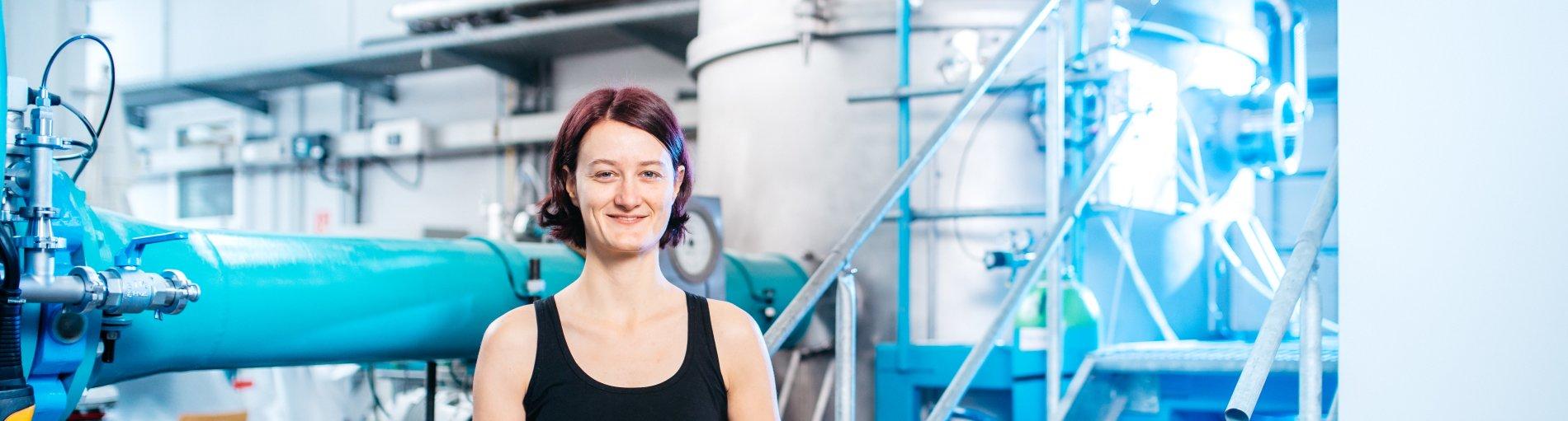 Eine Frau steht auf einer Treppe vor einem großen Tank.