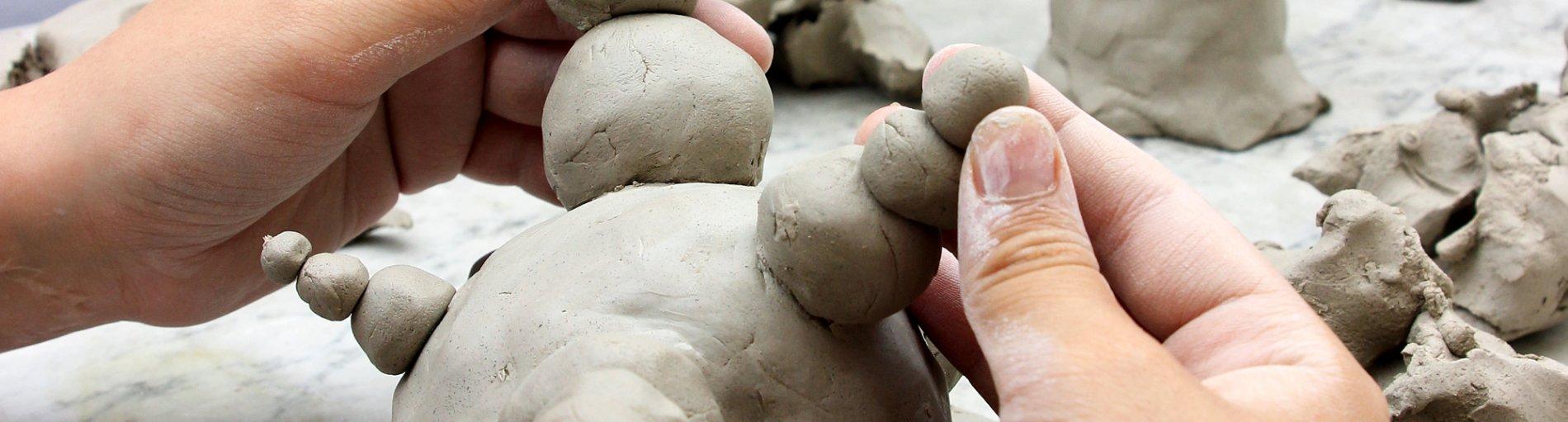 Kinderhände formen eine Figur aus Lehm.