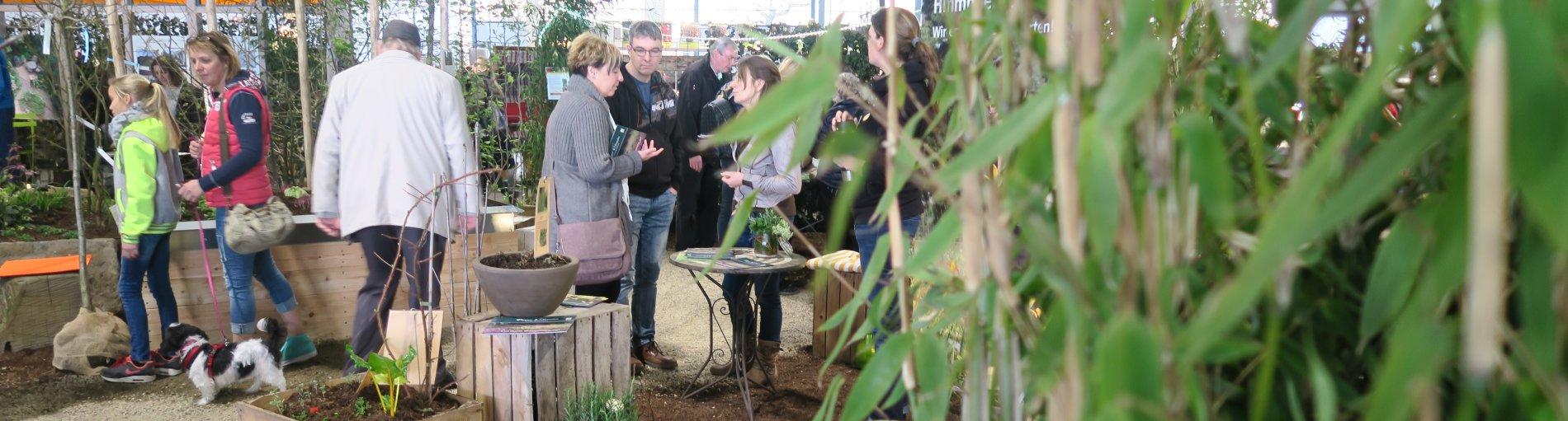 Mehrere Besucher der Veranstaltung Gartenträume Bremen schauen sich Pflanzen an und unterhalten sich.
