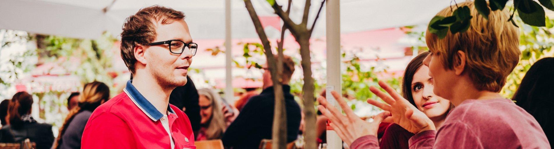 Ein Mann im Rollstuhl und zwei Frauen sitzen draußen in einem Straßencafé am Tisch und unterhalten sich.