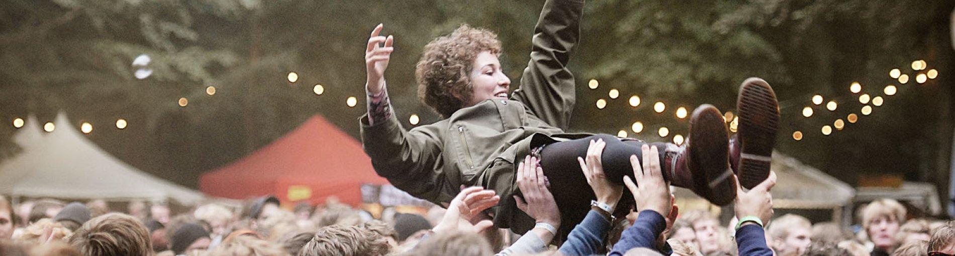 Eine Frau wird von der Konzertmenge getragen.