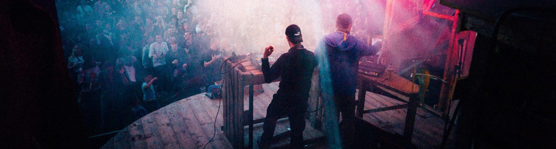 2 DJs stehen auf einer Bühne vor Publikum und legen auf.