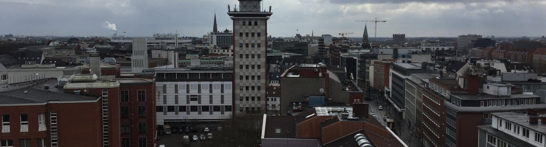 Zu sehen ist der Ausblick auf eine Stadt mit vielen Häusern und spitzen Türmen. Links im Bild ist ein freier Platz zu sehen, auf dem Autos parken. Rechts befindet sich eine Straße zwischen den Häusern, auf der Autos fahren. In der Mitte des Bildes ragt ein spitzer Turm zwischen den Häusern empor. Der Himmel ist blau und bewölkt.