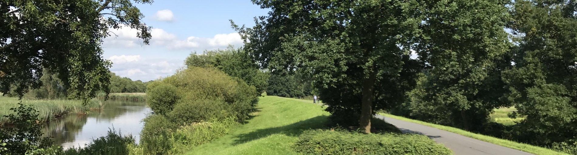 Rechts ist ein Weg auf einem Deich zu erkennen. Rechts im Bild ist ein Fluss zu sehen, der von grünen Bäumen und Wiesen umgeben ist.