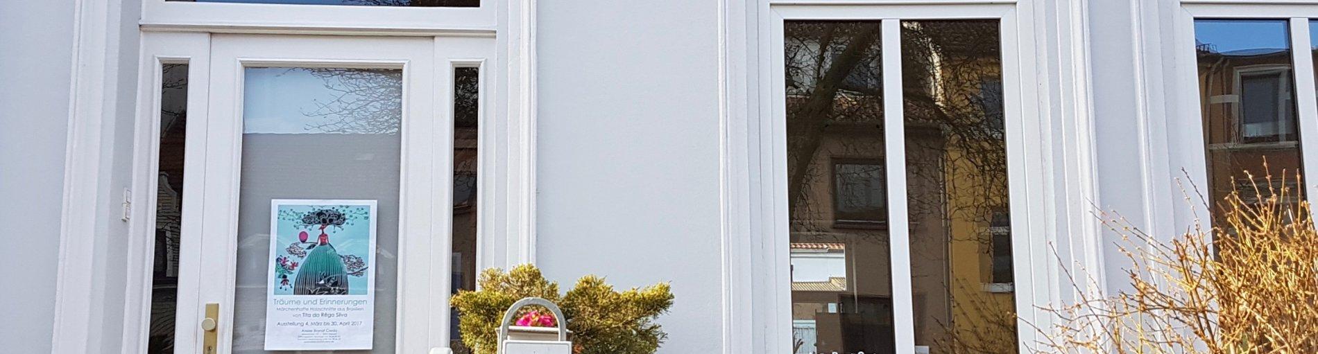 Außenansicht eines hell gestrichenen Hauses mit großen Fenstern und Glastür.