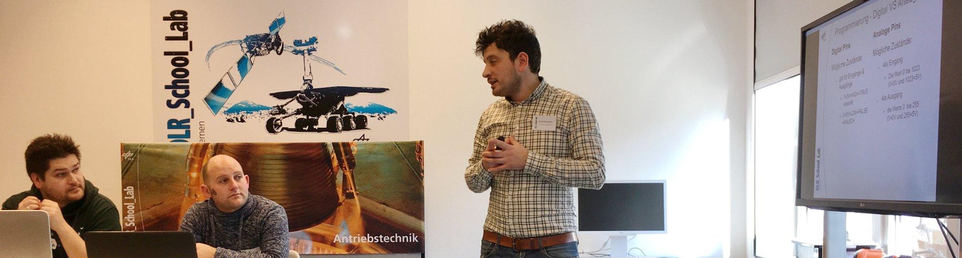 Links zwei Männer am Laptop, beide gucken den vor einem Bildschirm stehenden und redenden Mann an.
