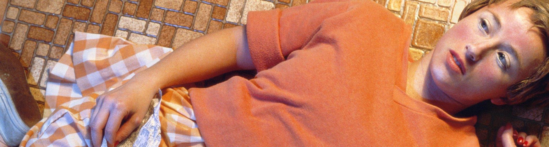 Eine Frau liegt in einem orangen Pulli und einem orange,weiß karierten Rock auf rötlichen Fliesen und hält einen Zettel in der Hand.
