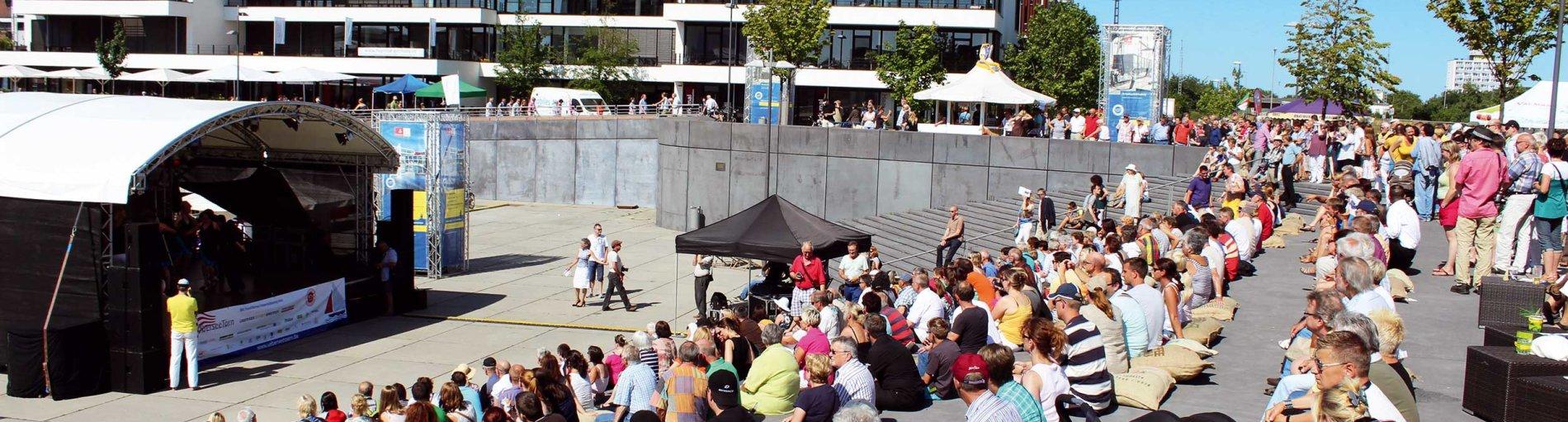 Eine breite Aufnahme des Europahafens mit viel Publikum und einer Bühne.