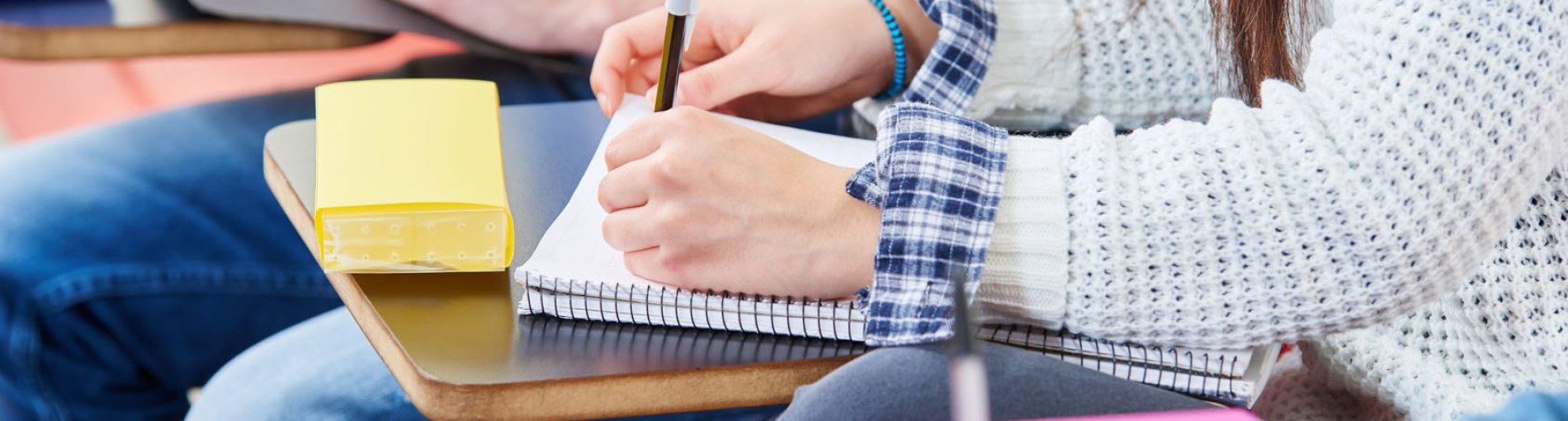 Eine junge Menschen sitzen in einer Reihe an Tischen und schreiben etwas auf einen Block.