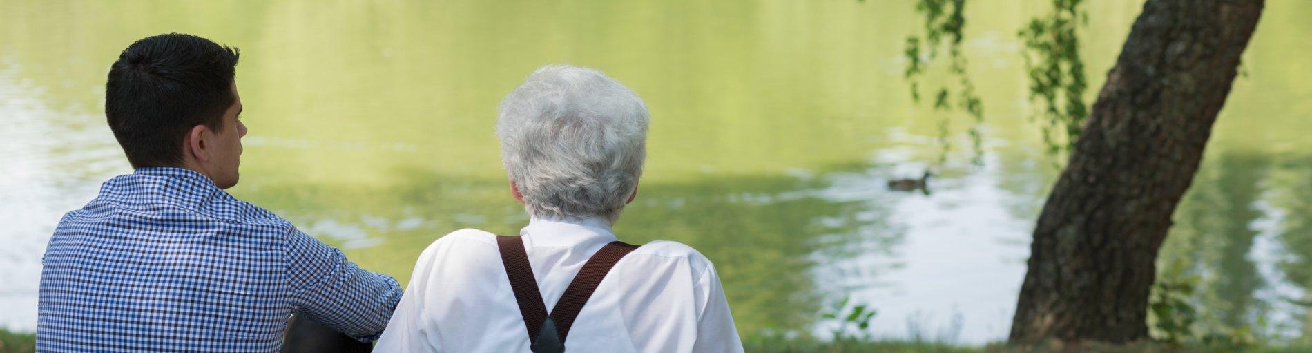 Junger und alter Mann blicken auf einen See