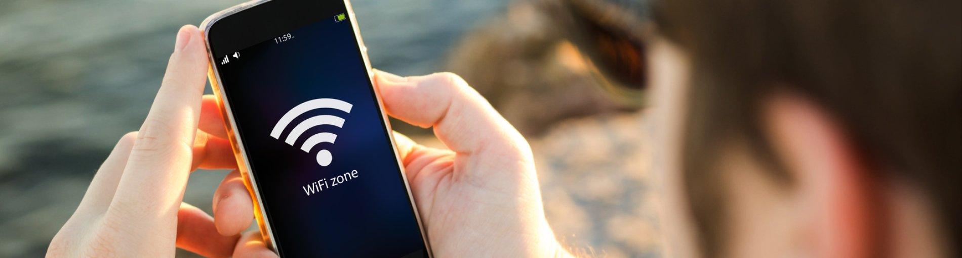 Ein Mann Hand hält ein Smartphone auf dem ein Wlan-Symbol zu sehen ist