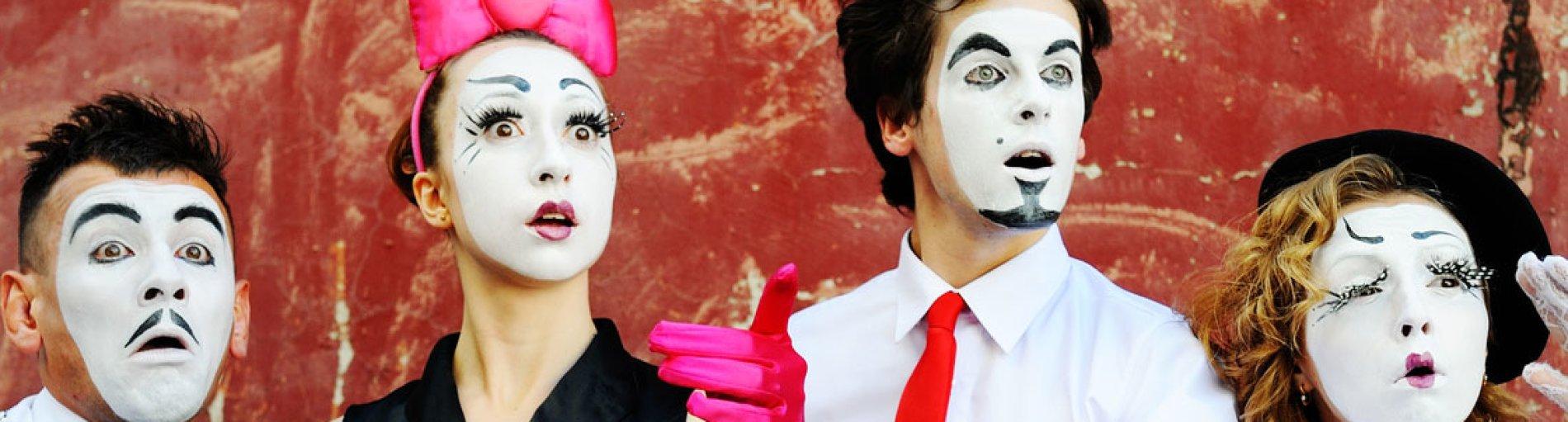 Zwei Schauspieler und zwei Schauspielerinnen mit schwarz-weiß geschminkten Gesichtern.