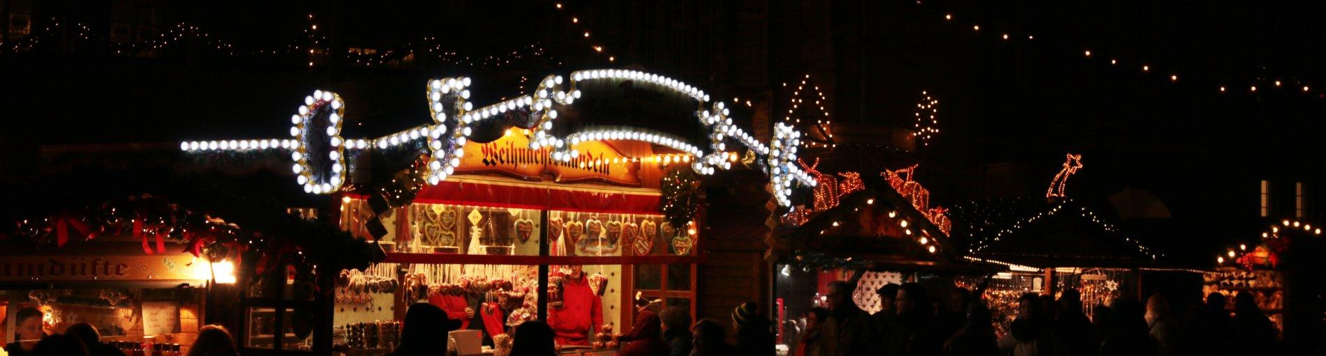 Buden auf einem Weihnachtsmarkt bei Nacht